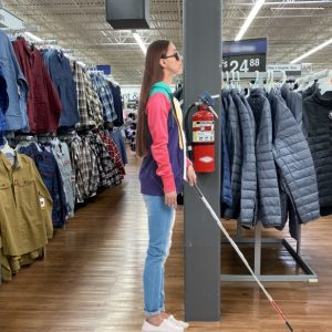 Blind person with cane at retail store